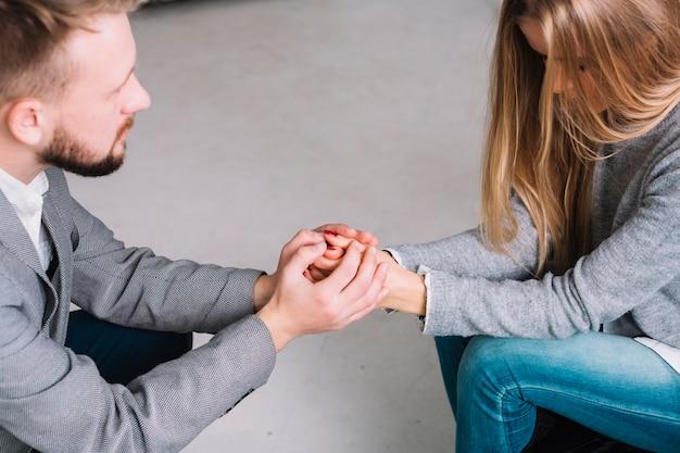 Primo piano dello psicologo che tiene le sue mani insieme mentre ascolta il suo paziente femminile Foto Gratuite