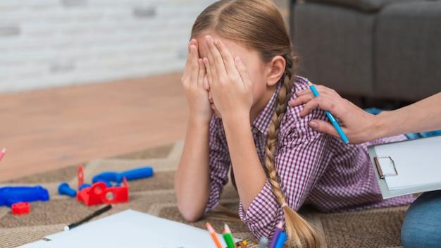 Primo piano dello psicologo femminile che consola la ragazza depressa che copre il suo fronte di mani Foto Gratuite
