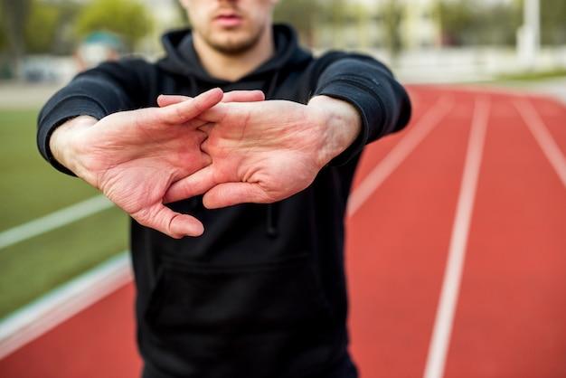 Primo piano dello sportivo maschio che allunga le sue mani sulla pista di corsa Foto Gratuite