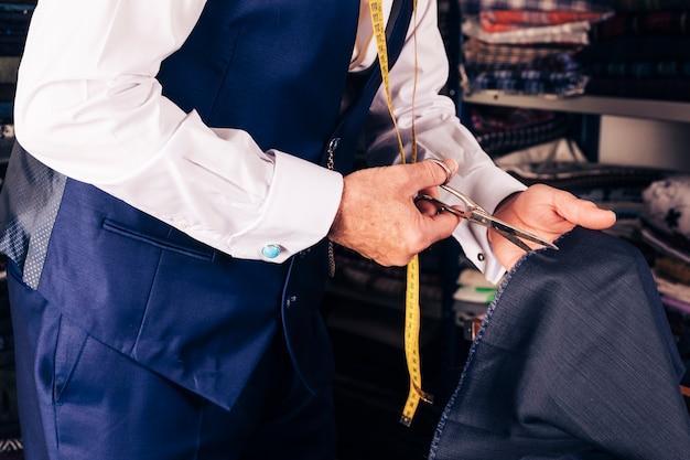 Primo piano dello stilista che taglia il tessuto con le forbici Foto Gratuite