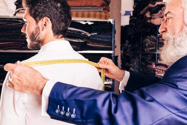 Primo piano dello stilista senior che prende misura del suo cliente Foto Gratuite