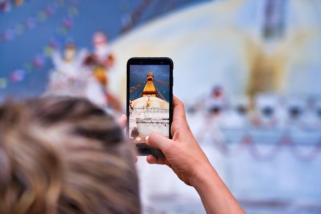 Primo piano dello stupa di boudhanath a kathmandu. la foto scattata da una donna occidentale da dietro. bionda con i capelli raccolti. scattare foto con uno smartphone. bokeh Foto Premium