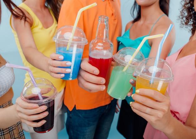 Primo piano di 4 bicchieri di plastica e bottiglia con diversi colori di succo Foto Premium