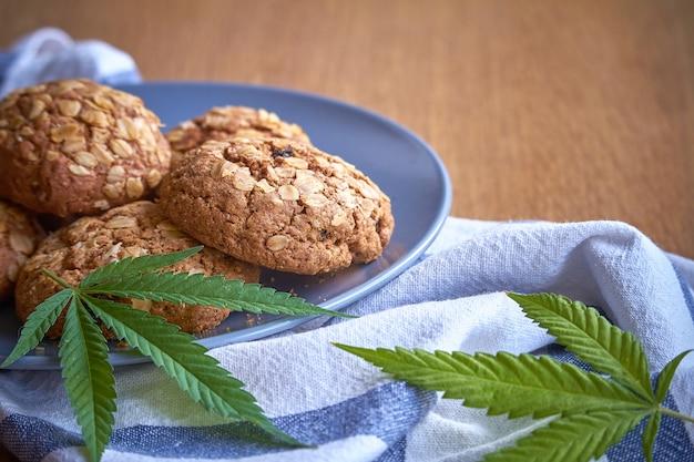 Primo piano di alcuni biscotti del vaso di farina d'avena su un piatto grigio su un asciugamano a strisce su una superficie di legno leggera. Foto Premium