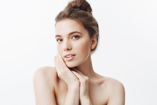 Primo piano di attraente giovane donna dai capelli scuri con taglio di capelli bun e spalle nude tenendo le mani vicino al viso, con espressione del viso rilassato e calmo. Foto Gratuite