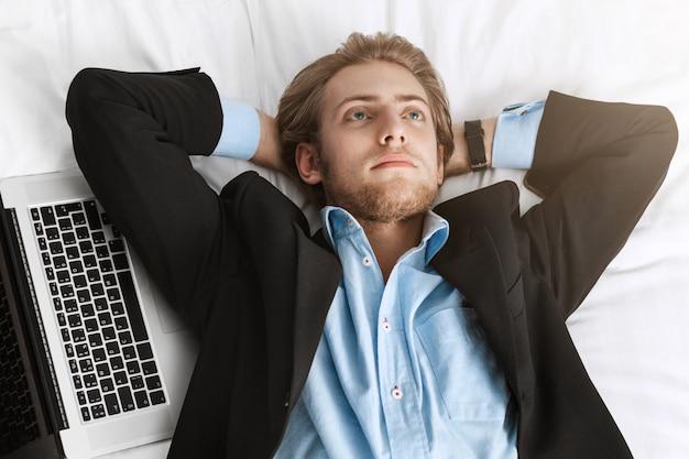 Primo piano di bel uomo d'affari con la barba in abito alla moda sdraiato sulla schiena con le mani sotto la testa con il portatile vicino a lui, guardando al rialzo, pensando alla riunione di domani. Foto Gratuite