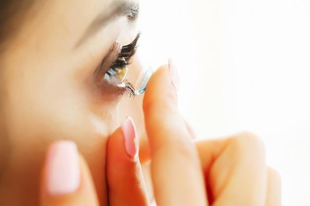 Primo piano di bella donna che applica lente dell'occhio in occhio Foto Premium
