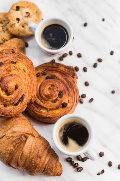 Primo piano di caffè e croissant con chicco di caffè su marmo Foto Gratuite