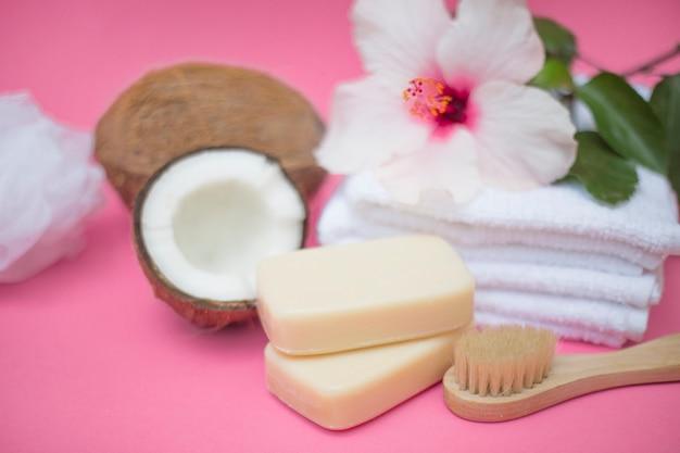 Primo piano di cocco; sapone; spazzola; fiore e asciugamani su sfondo rosa Foto Gratuite