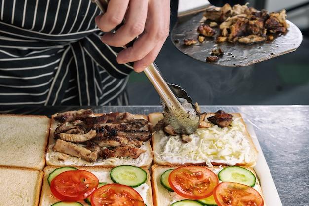 Primo piano di cottura deliziosi panini con carne alla griglia, maionese, pomodoro, formaggio e cetriolo Foto Premium