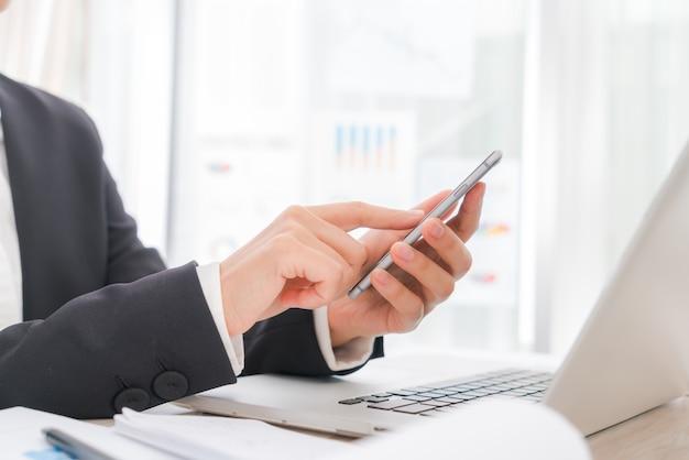Primo piano di donna d'affari mano digitando sulla tastiera del computer portatile con m Foto Gratuite