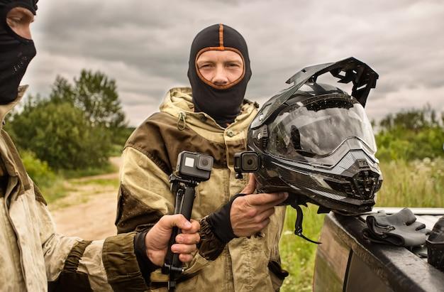 Primo piano di due uomini all'aperto indossando caschi passamontagna e divise moto. Foto Premium