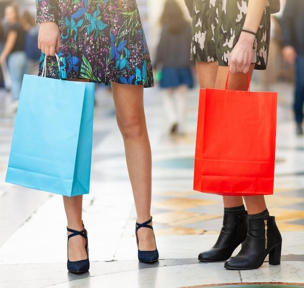 Primo piano di gambe e borse della spesa. Foto Premium