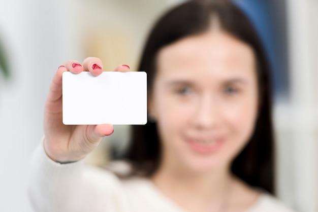 Primo piano di giovane donna di affari di defocus che mostra biglietto da visita bianco Foto Gratuite