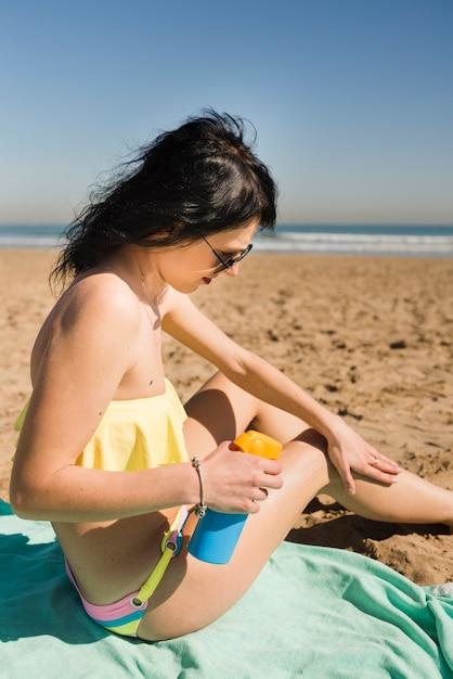 Primo piano di giovane donna seduta sulla spiaggia applicando la crema solare sul suo corpo Foto Gratuite