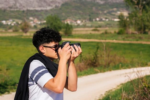 Primo piano di giovane fotografo che cattura la fotografia della natura Foto Gratuite