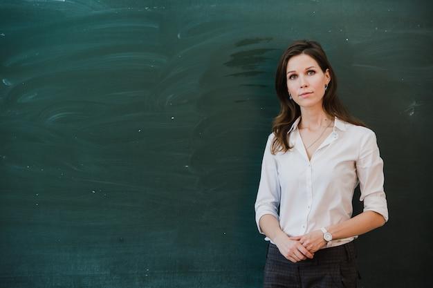 Primo piano di giovane insegnante femminile contro la lavagna nella classe Foto Premium
