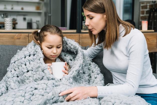 Primo piano di giovane madre prendersi cura di sua figlia malata tenendo la tazza in mano Foto Gratuite