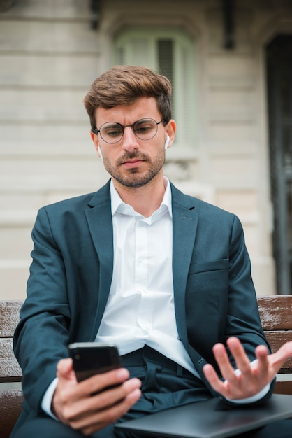 Primo piano di giovane uomo d'affari parlando sul cellulare con auricolare wireless nelle sue orecchie Foto Gratuite