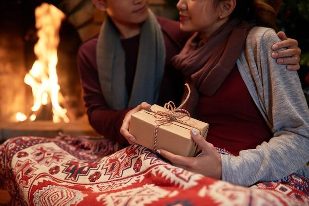 Primo piano di giovani coppie che stringono a sé al camino con un regalo in mani femminili Foto Gratuite