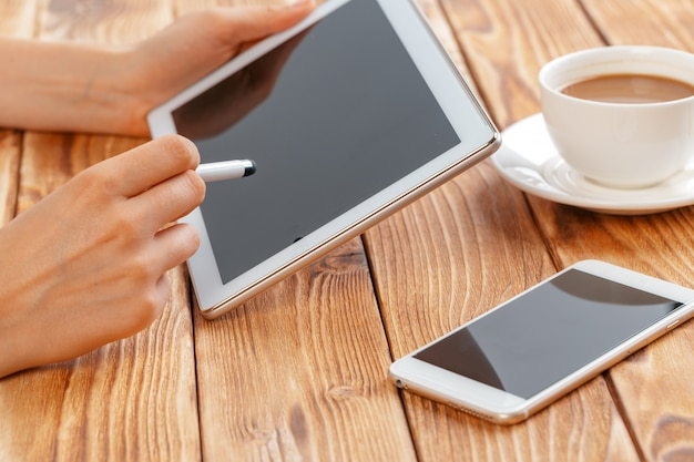 Primo piano di giovani mani femminili che tengono compressa digitale e bere mattina macchiato. Foto Premium