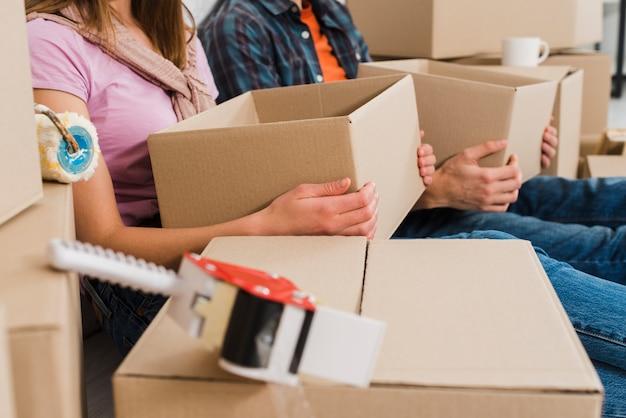 Primo piano di giovani scatole di cartone della tenuta delle coppie a disposizione alla loro nuova casa Foto Gratuite