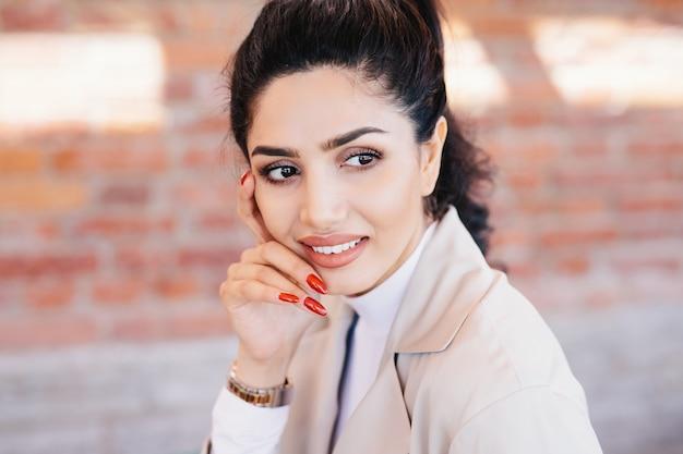 Primo piano di glamour donna bruna con sopracciglia sottili, occhi scuri con lunghe ciglia Foto Premium
