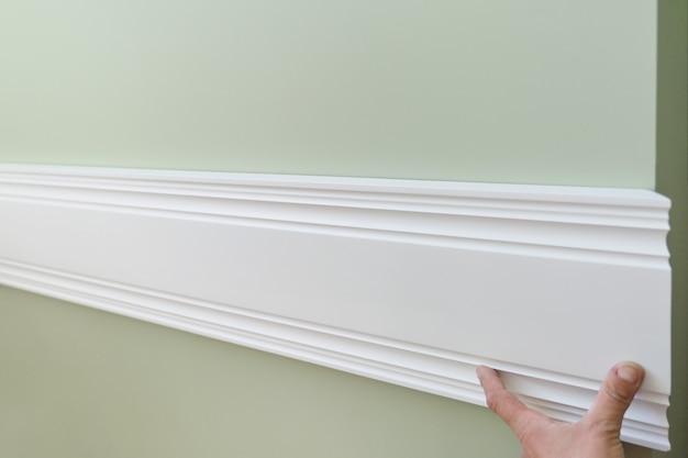 Primo piano di incollaggio del pannello della plancia dipinto bianco di legno sulla parete Foto Premium