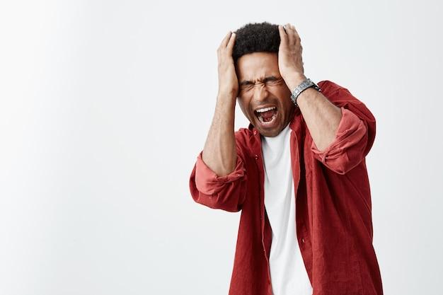 Primo piano di infelice maturo africana ta-skinned uomo con acconciatura riccia in bianco casual camicia e camicia rossa tenendo la testa con le mani, lottando da mal di testa dopo la musica ad alto volume alla festa. Foto Gratuite