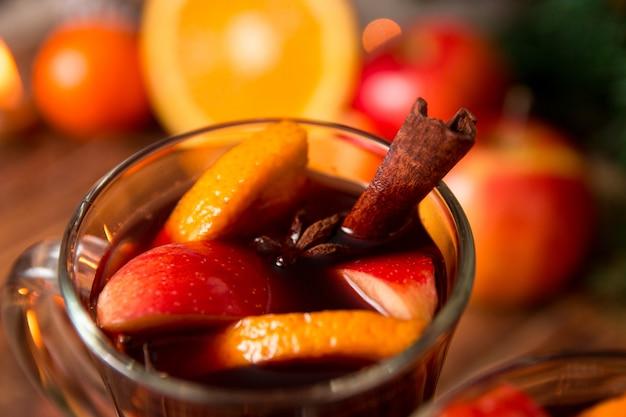 Primo piano di natale vin brulè con frutta, candele e spezie. Foto Premium
