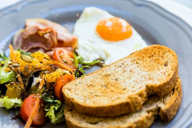 Primo piano di pane tostato; uova fritte; insalata e pancetta servita su piatto di ceramica Foto Gratuite