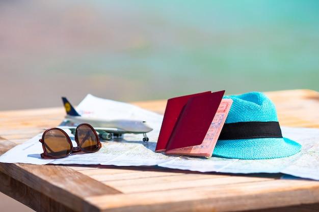 Primo piano di passaporti, aeroplanino giocattolo, occhiali da sole sulla mappa Foto Premium