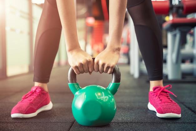 Primo piano di persone che si esercitano con kettlebell in palestra allenamento sportivo e fitness Foto Premium