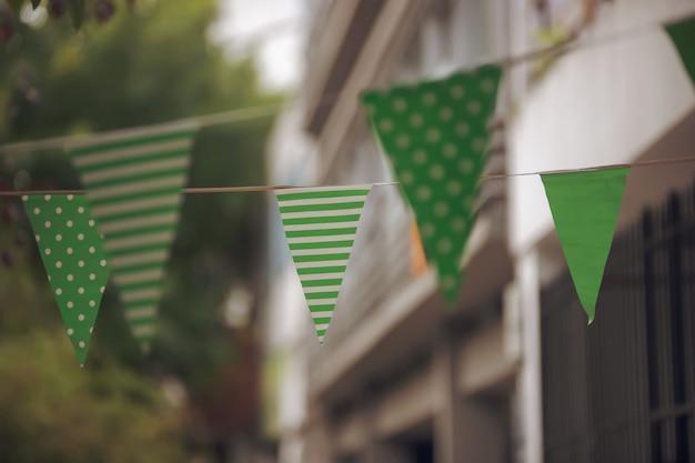 Primo piano di piccole bandiere verdi con punti bianchi e strisce il giorno di san patrizio Foto Gratuite