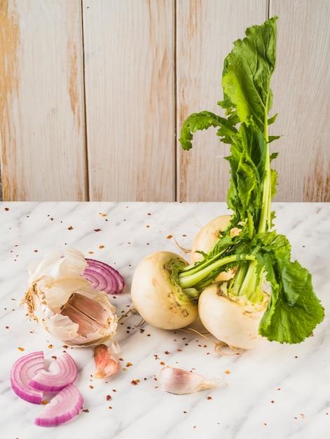 Primo piano di rapa; fetta di cipolla e spicchi d'aglio sulla superficie del marmo Foto Gratuite