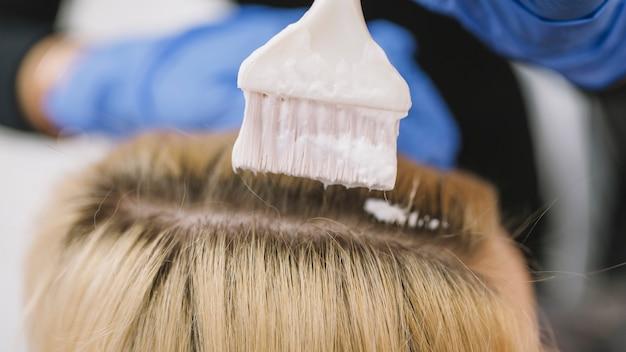 Primo piano di stilista che tinge i capelli del cliente Foto Gratuite