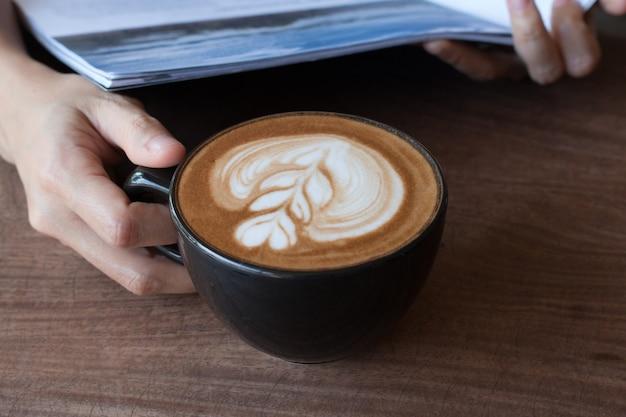 Primo piano di tazza di caffè caldo arte latte sul tavolo di legno