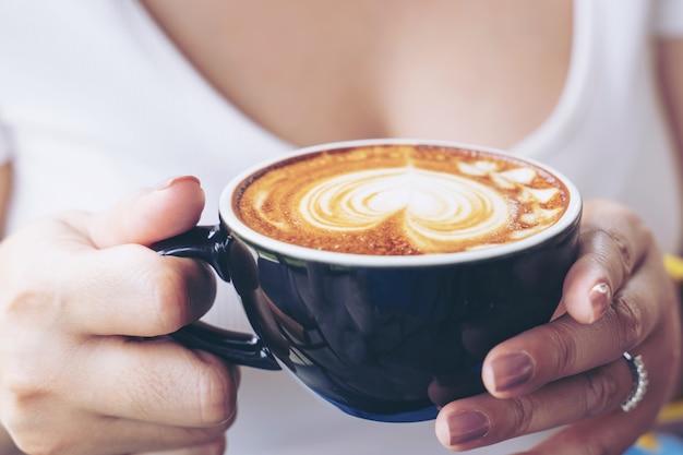 Primo piano di un arte del latte della tazza di caffè sulla mano della donna in caffè della caffetteria Foto Gratuite