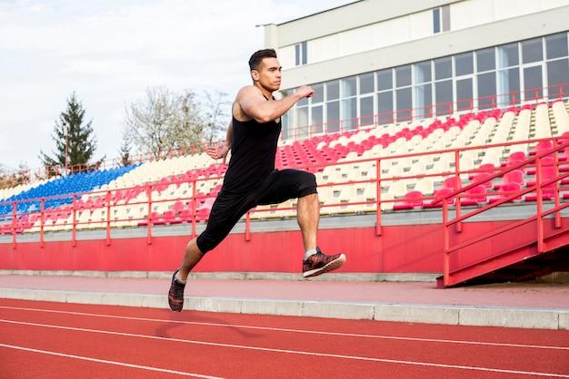 Primo piano di un atleta maschio che funziona sulla pista di corsa allo stadio Foto Gratuite