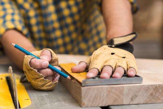 Primo piano di un carpentiere che misura un blocco di legno facendo uso del righello sul tavolo da lavoro Foto Gratuite