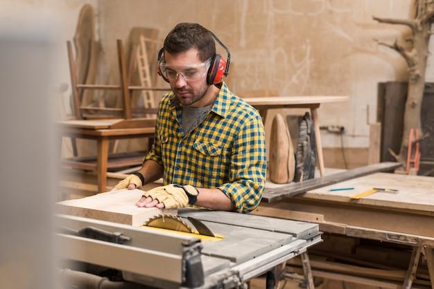 Primo piano di un carpentiere maschio che taglia un blocco di legno con la sega circolare in tavola Foto Gratuite