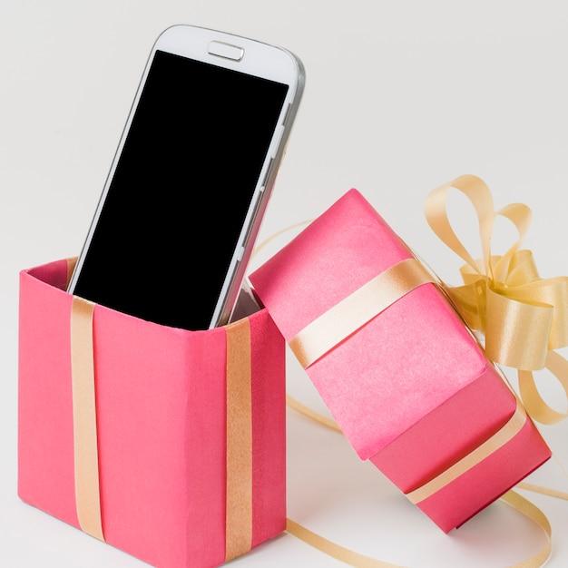 Primo piano di un cellulare in confezione regalo rosa decorato contro superficie bianca Foto Gratuite