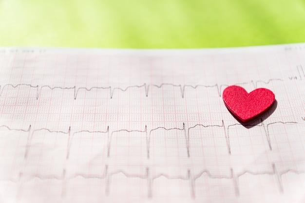 Primo piano di un elettrocardiogramma in forma di carta con cuore in legno rosso. carta ecg o ecg. concetto medico e sanitario. Foto Premium