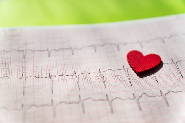 Primo piano di un elettrocardiogramma in forma di carta con cuore in legno rosso. carta ecg o ecg su nero. concetto medico e sanitario. Foto Premium