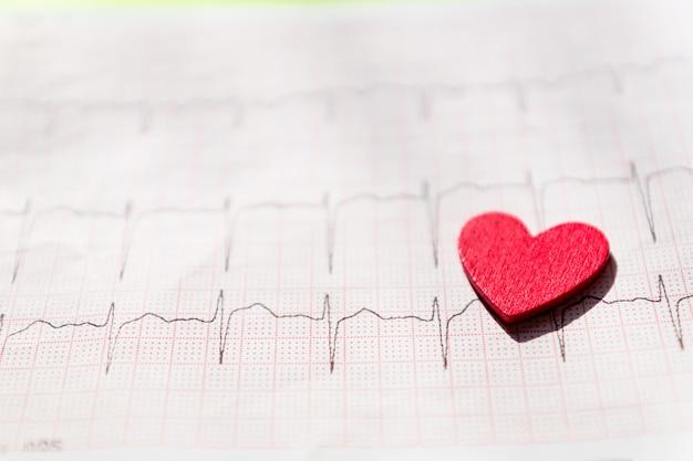 Primo piano di un elettrocardiogramma in forma di carta con cuore in legno rosso. trama di sfondo carta ecg o ecg. concetto medico e sanitario. Foto Premium