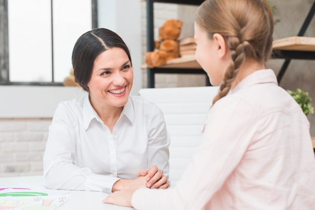 Primo piano di un felice giovane femmina psicologo e ragazza parlando a vicenda durante la sessione di terapia Foto Gratuite