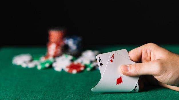Primo piano di un giocatore che tiene una carta di due assi sul tavolo da poker Foto Gratuite