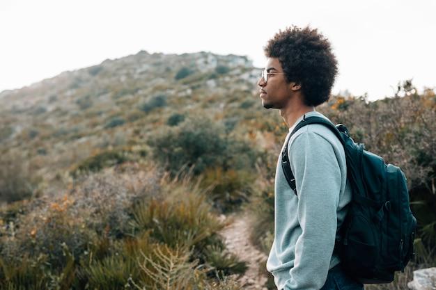Primo piano di un giovane africano con il suo zaino che sta davanti alla montagna Foto Gratuite
