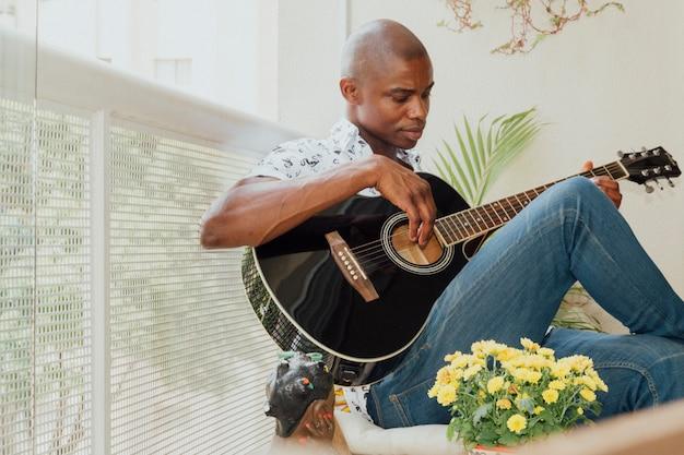 Primo piano di un giovane africano suonare la chitarra nel balcone Foto Gratuite