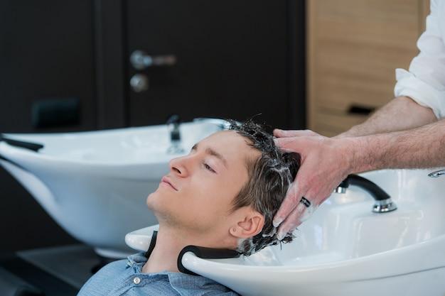 Primo piano di un giovane che fa lavare i capelli nel salone di parrucchiere Foto Premium